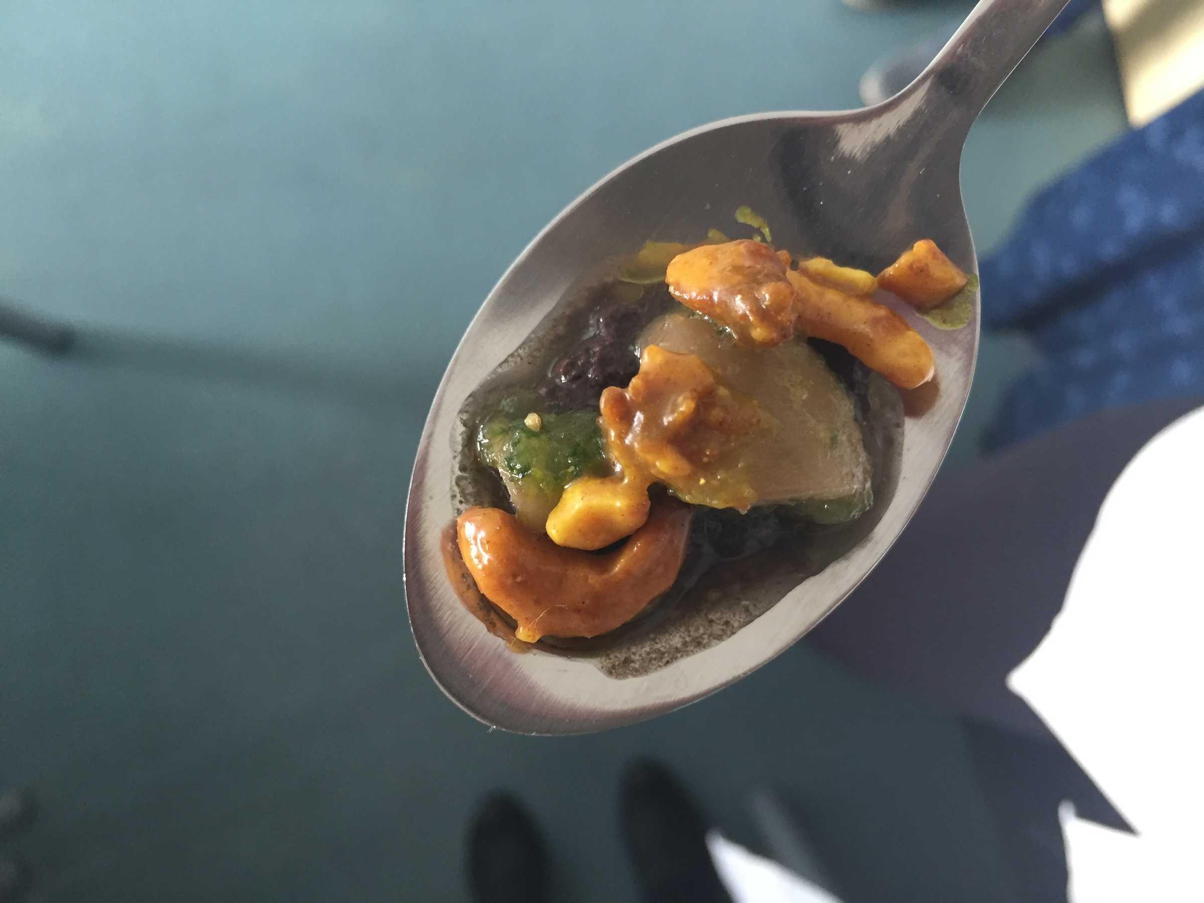 Ein Löffel mit Champignons, Olivenpaste und Cashewkernen.