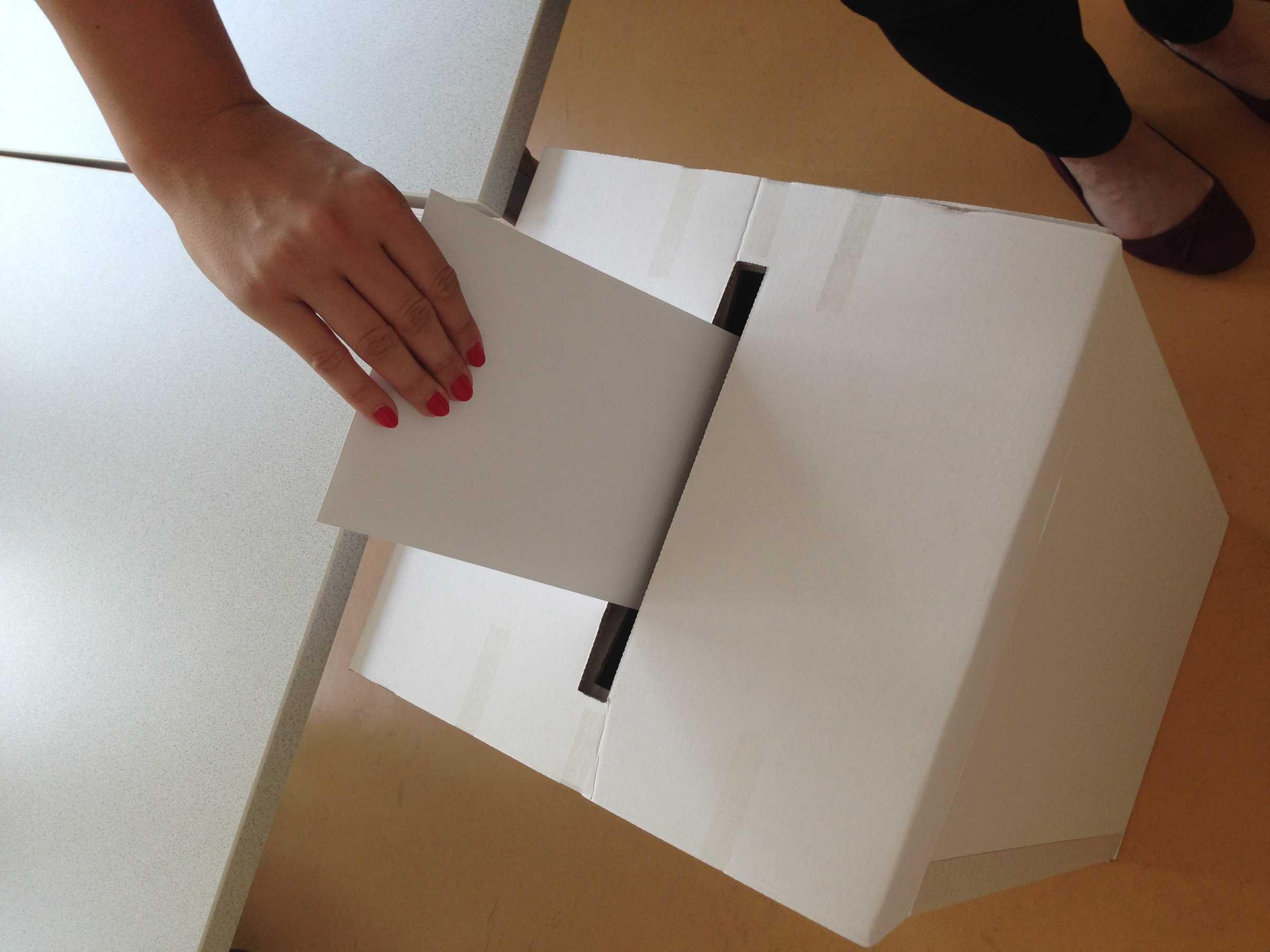 Einwurf des Kuvers in die Wahlurne.
