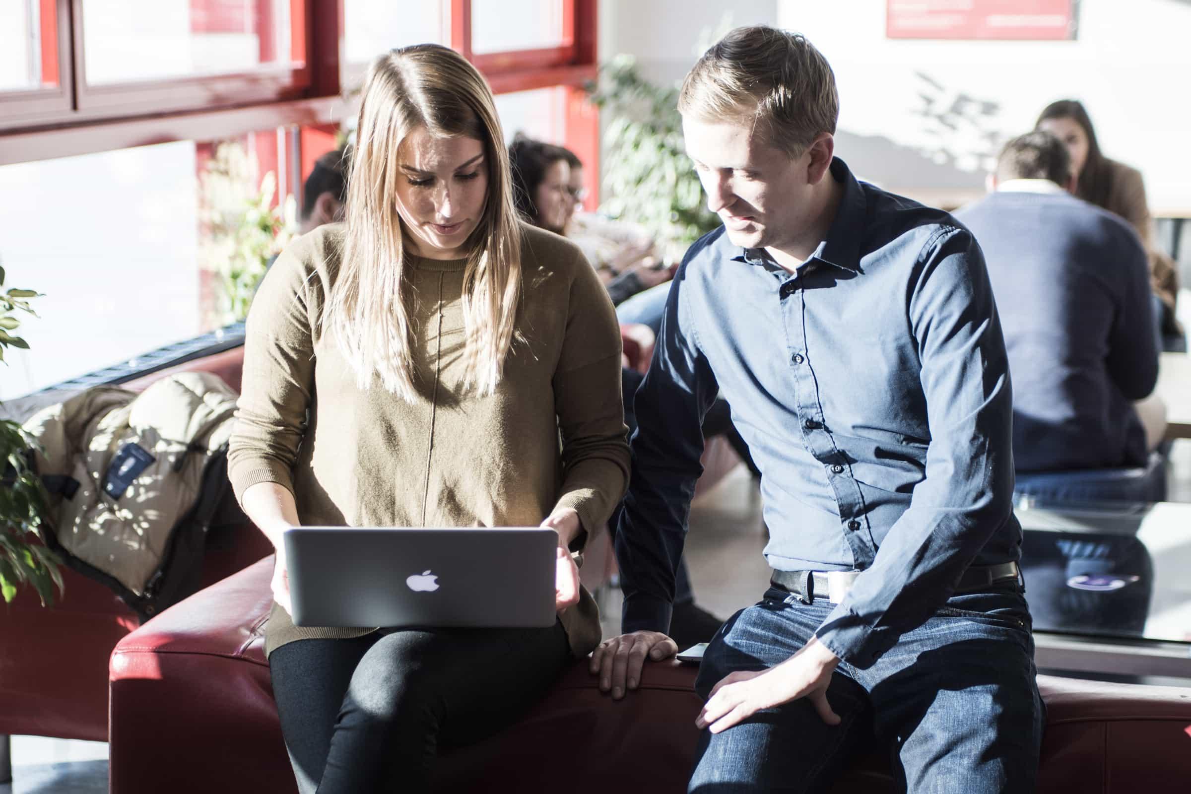 Zwei Studierende auf einer Couch mit Laptop.