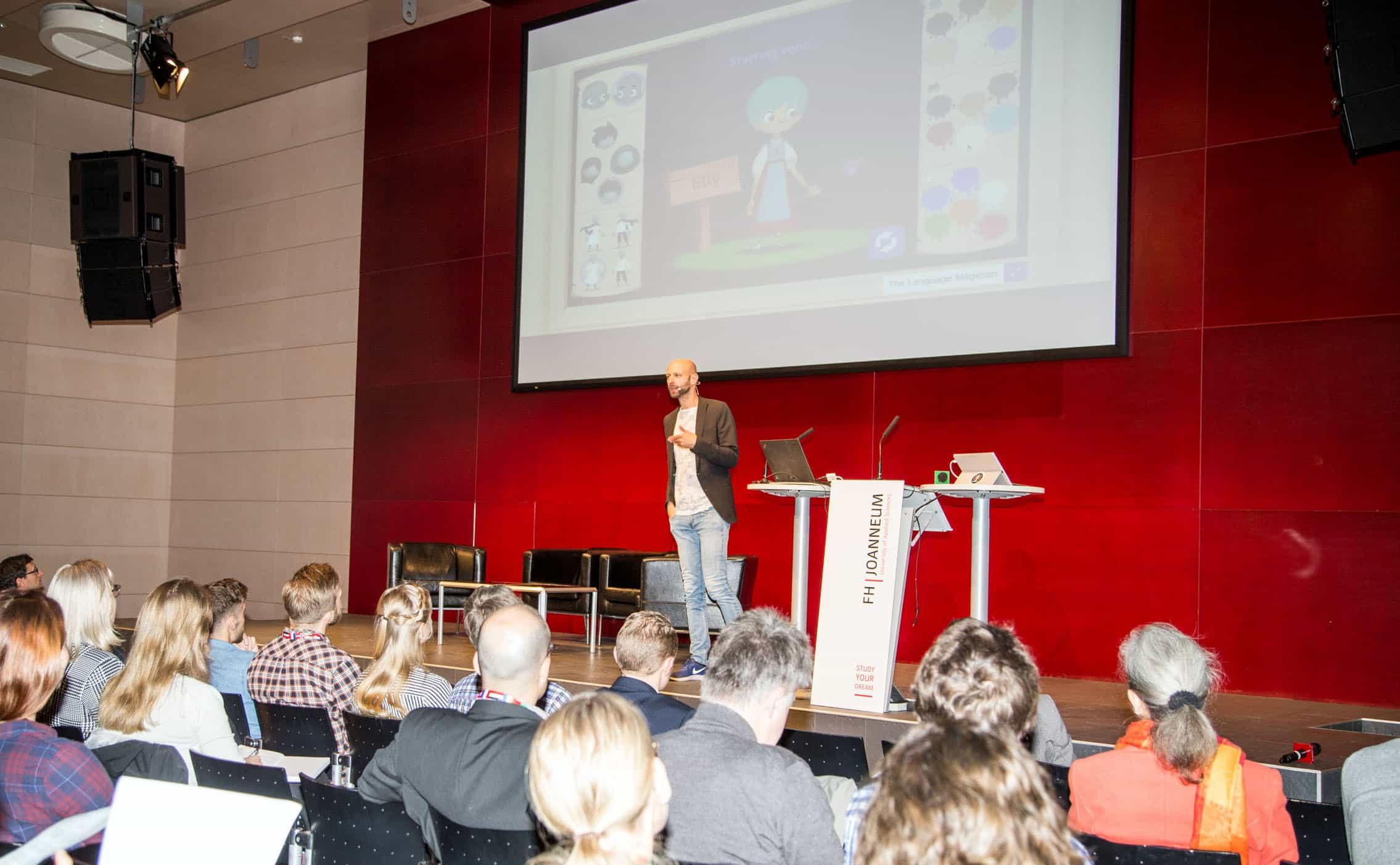 Der Keynote Speaker mit Präsentation im Hintergrund.