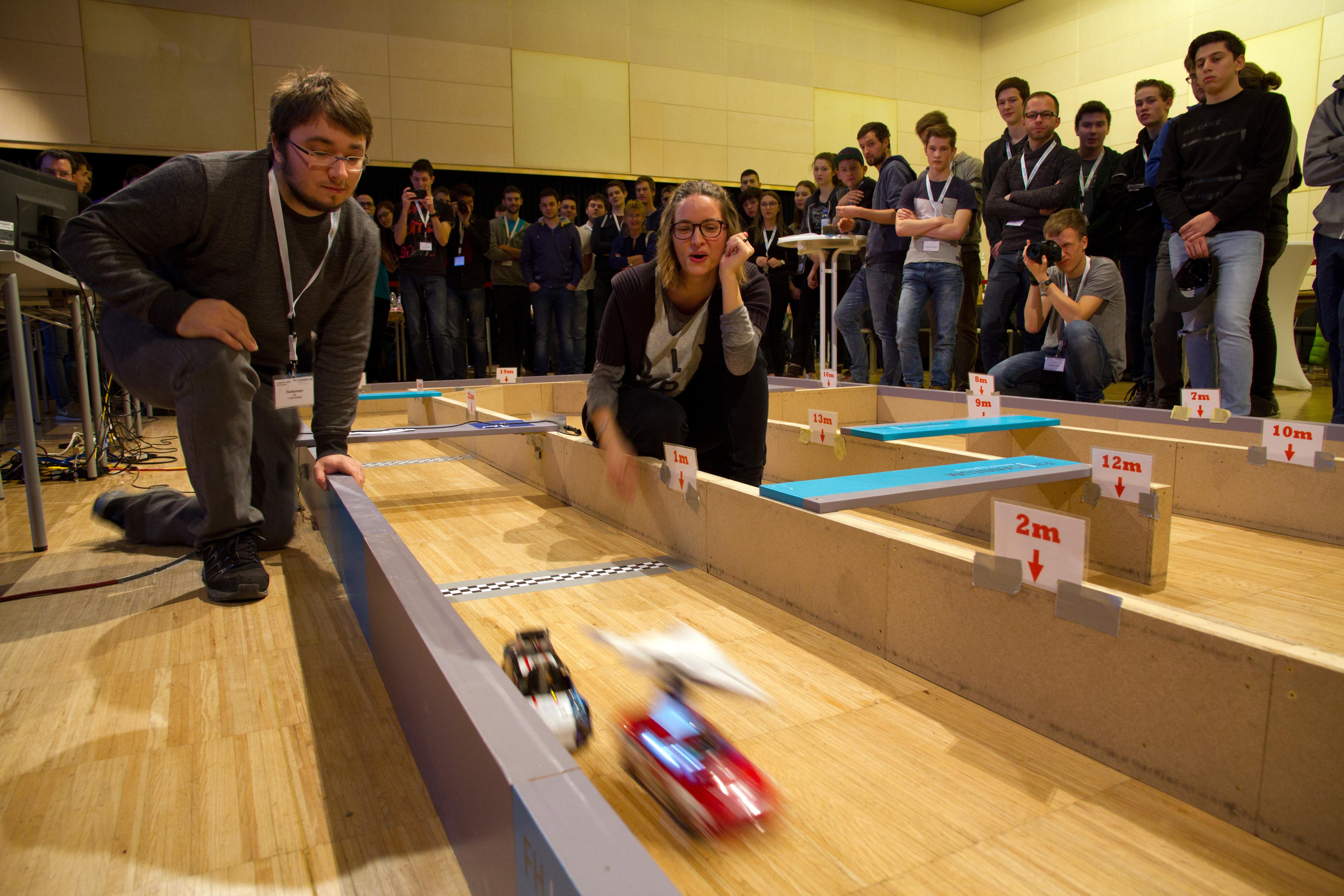 Schülerinnen und Schüler rund um die Strecke aus Holz.