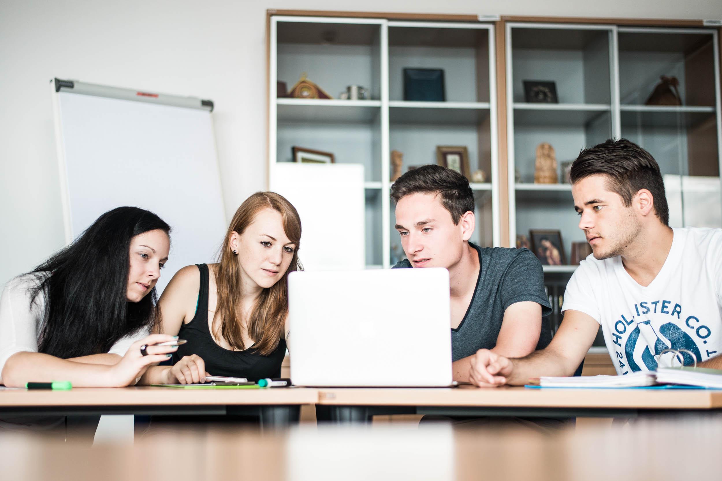 Studierende sitzen vor einem geöffneten Laptop.