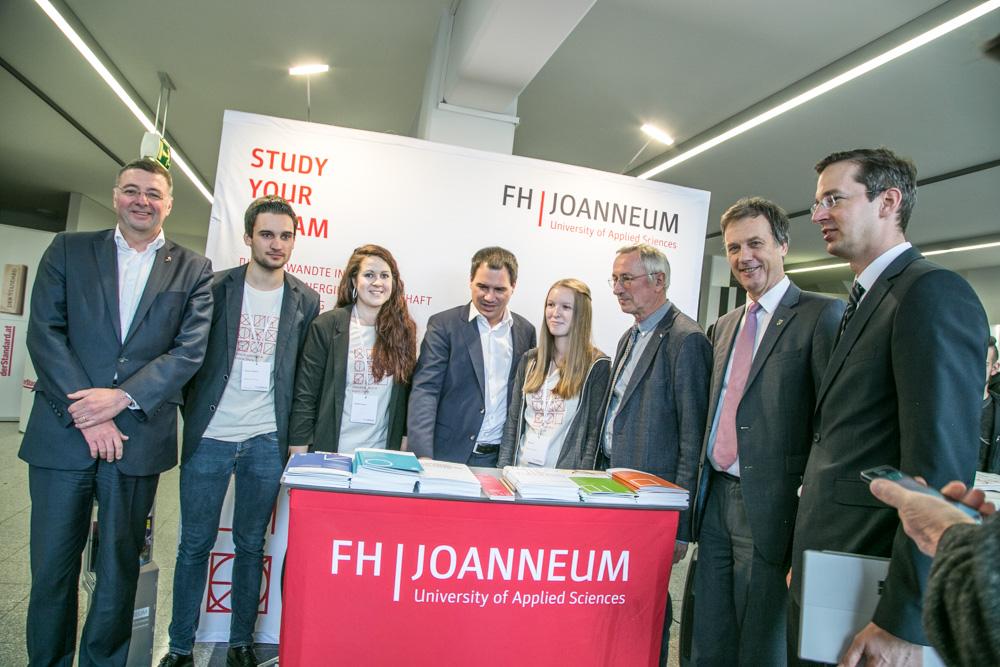 Personen rund um einen Tisch mit Informationsmaterial zur FH JOANNEUM