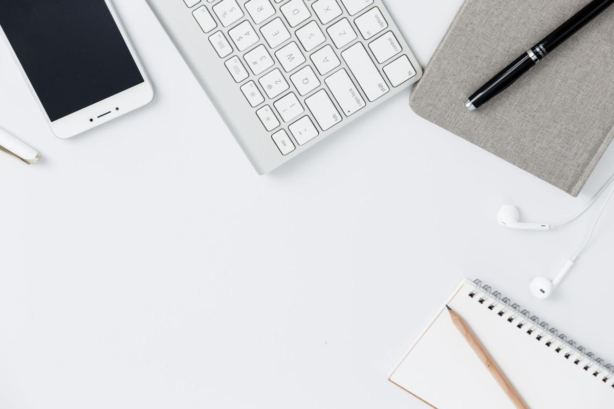 Smartphone, Tastatur und Block auf einem Tisch