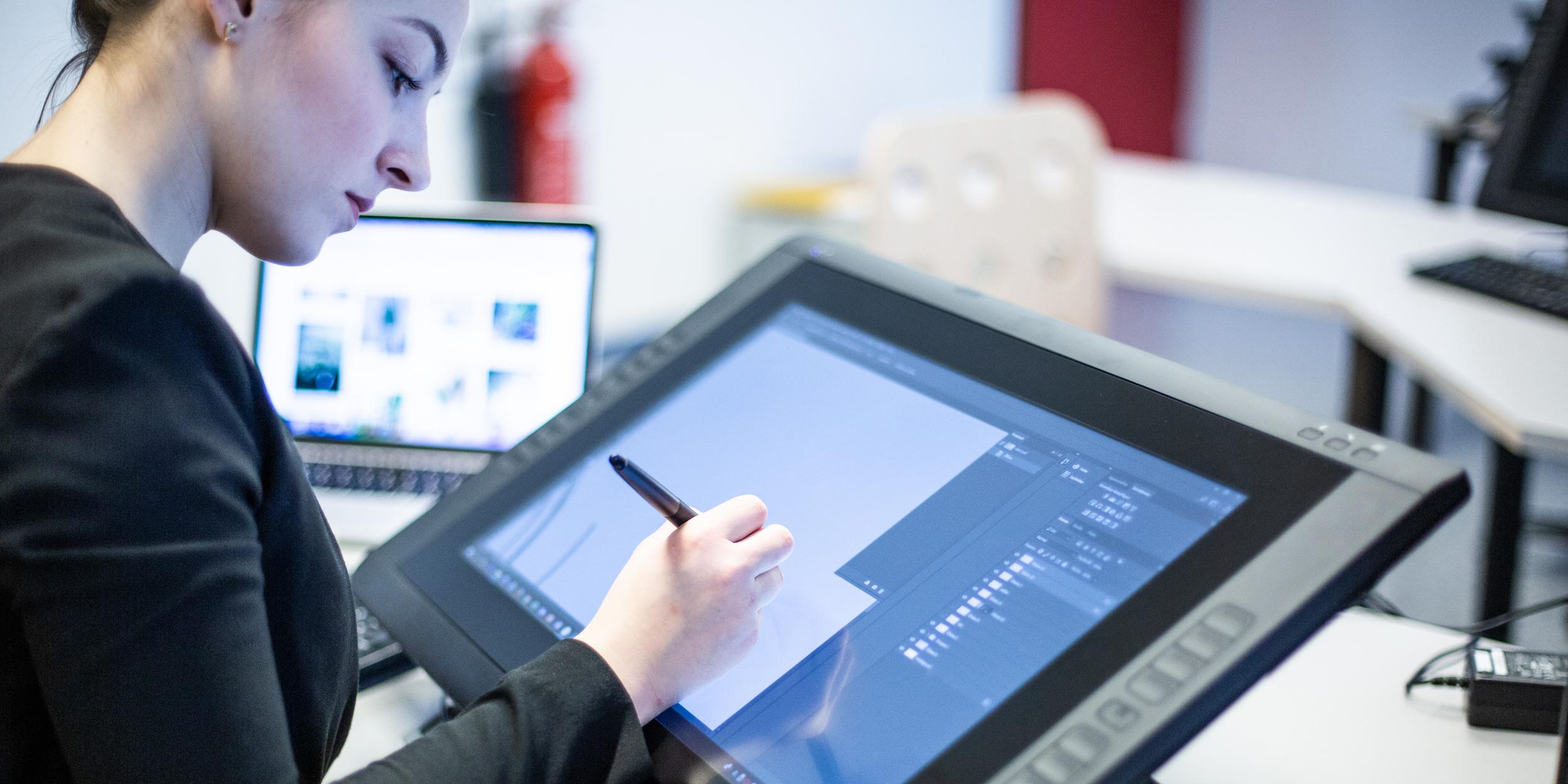 Anna Petritsch zeichnet mit der Hand einen Design-Entwurf auf einen Computerbildschirm.