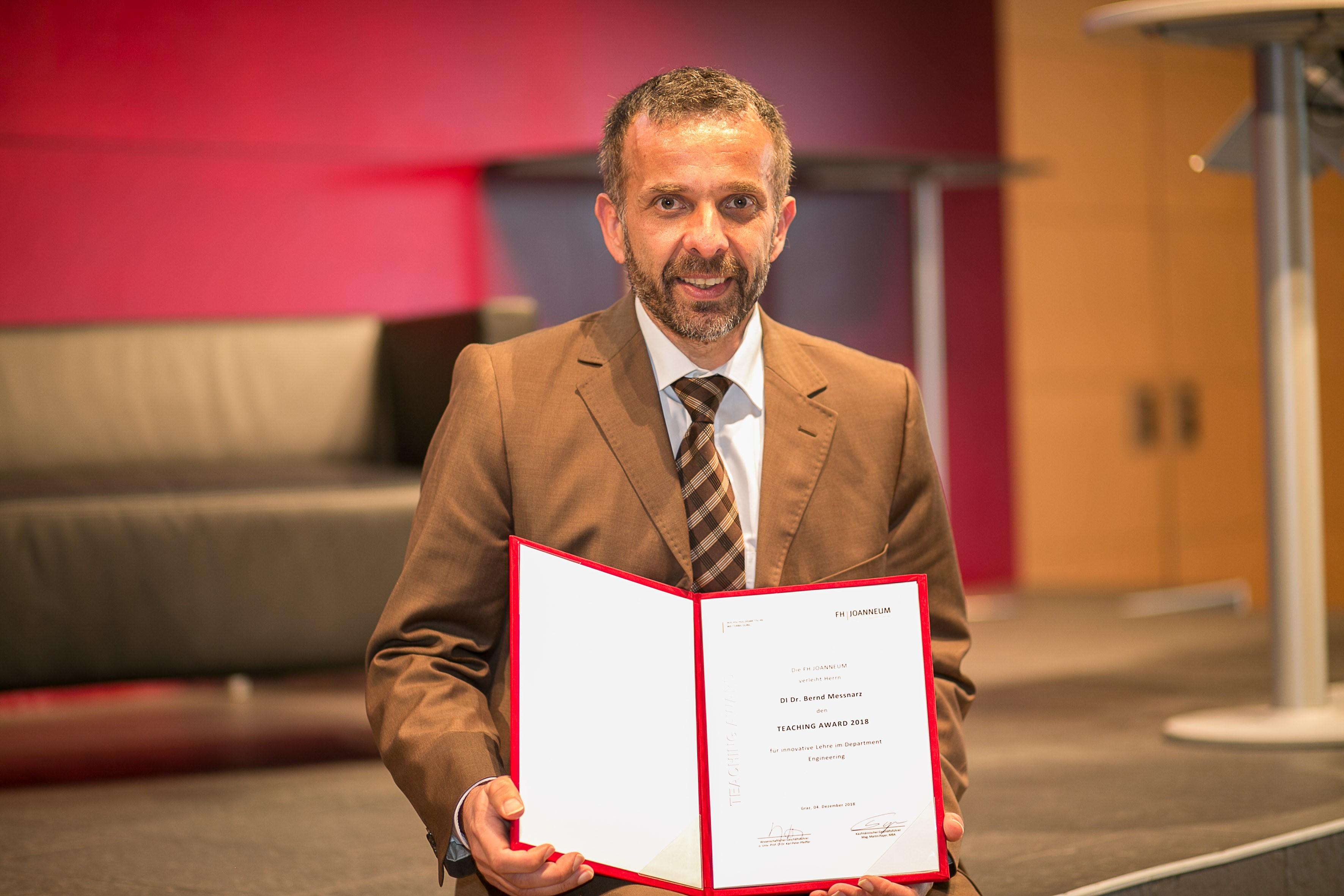 Bernd Messnarz hält den Teaching Award 2018 in die Kamera.