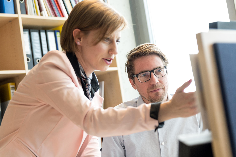 Zwei Arbeitende vor einem Rechner.