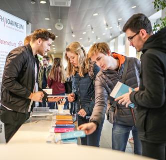 Interessierte Besucherinnen und Besucher holen sich Departmentfolder am Informationsstand.