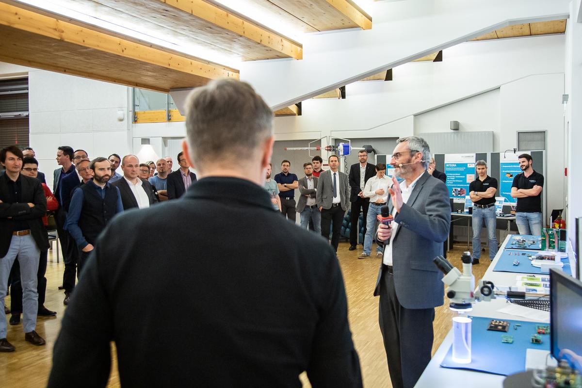 Hubert Berger neben elektronischen Geräten mit Publikum im Hintergrund