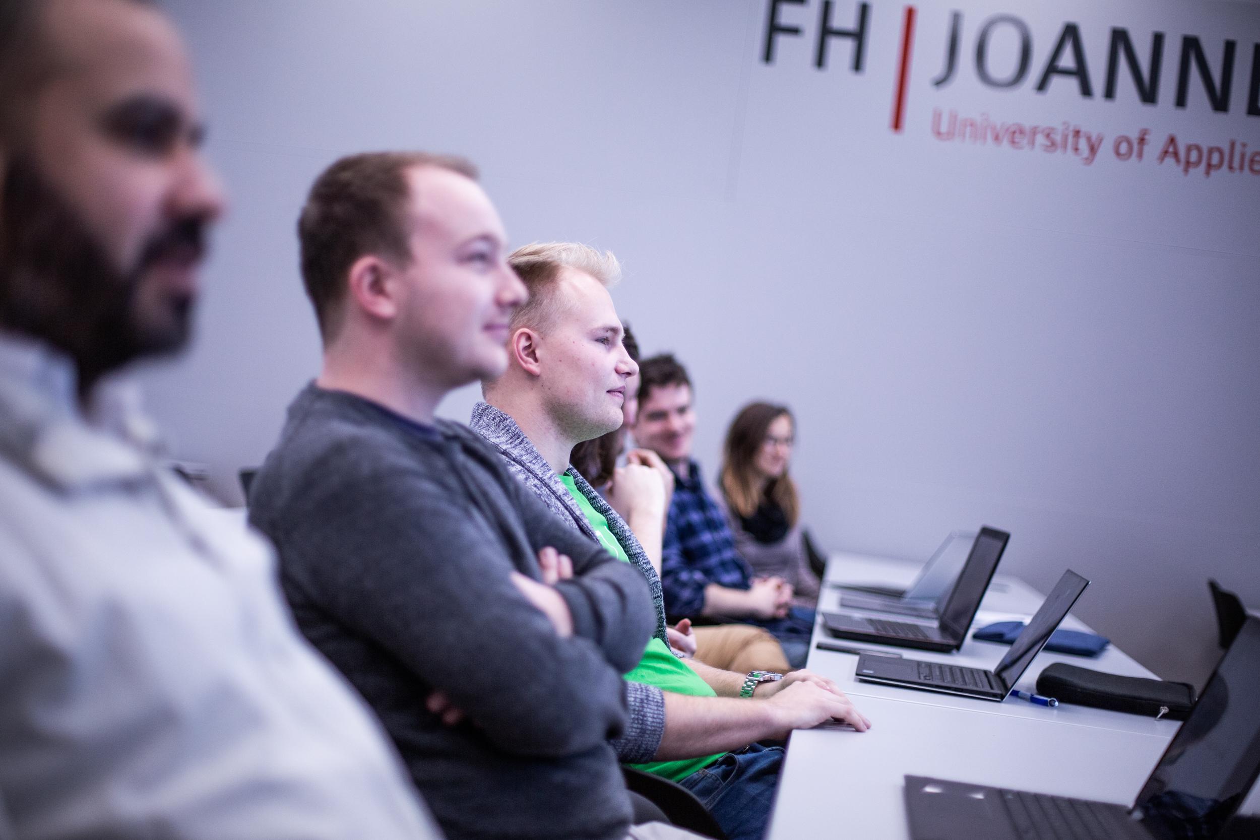 Kevin Stessel sitzt mit Studierenden in einer Vorlesung.