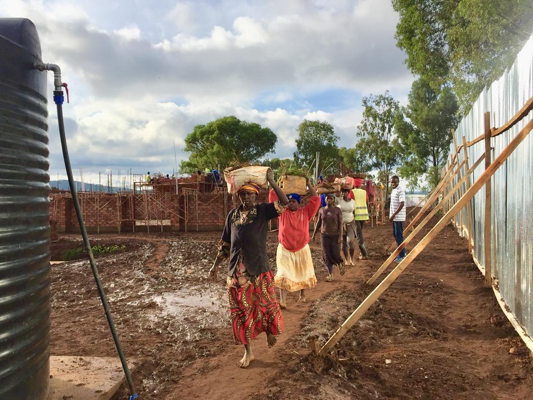Frauen schleppen Materialien auf einer Baustelle.