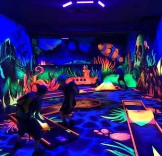 Kinder in einem dunklen Raum, der mit Neonlichtern beleuchtet ist.