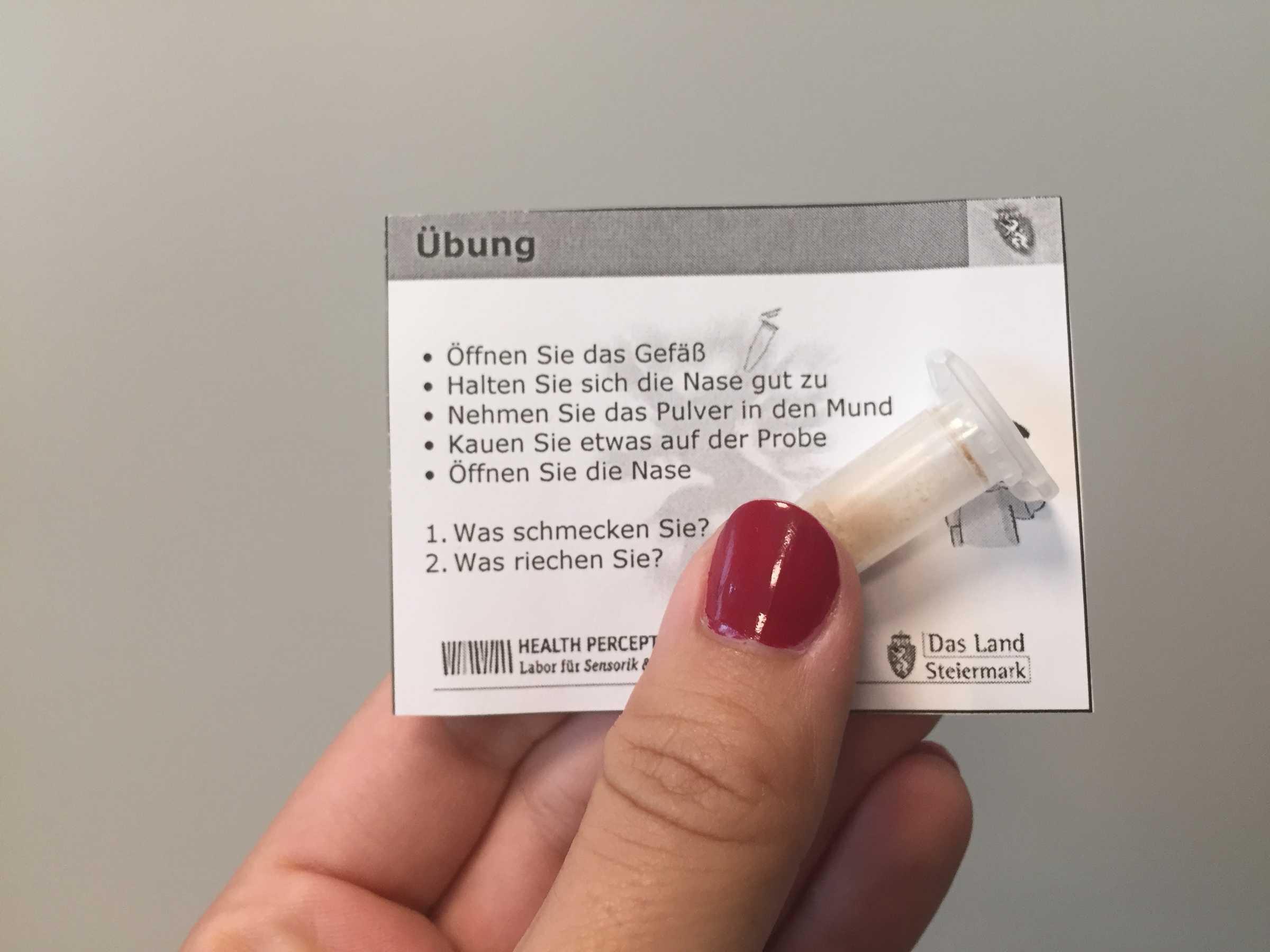 Die Übungsanleitung mit einem Plastikröhrchen, in dem eine Gewürzmischung enthalten ist.