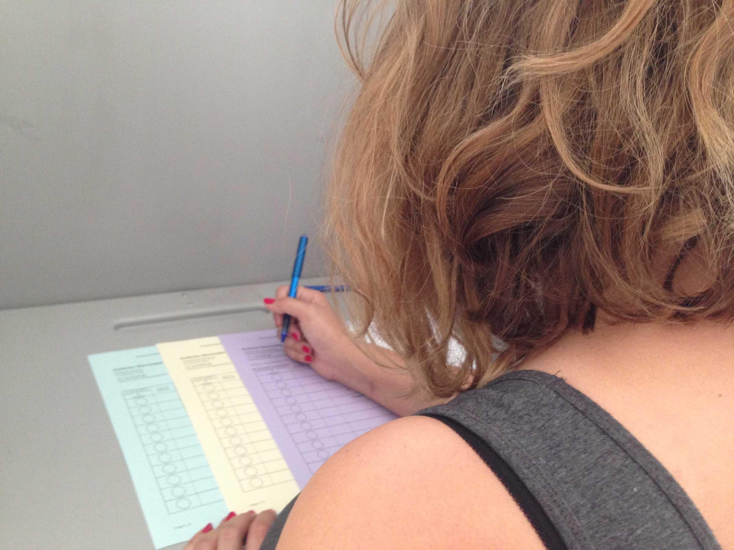 Blick über die Schulter einer Wählenden.