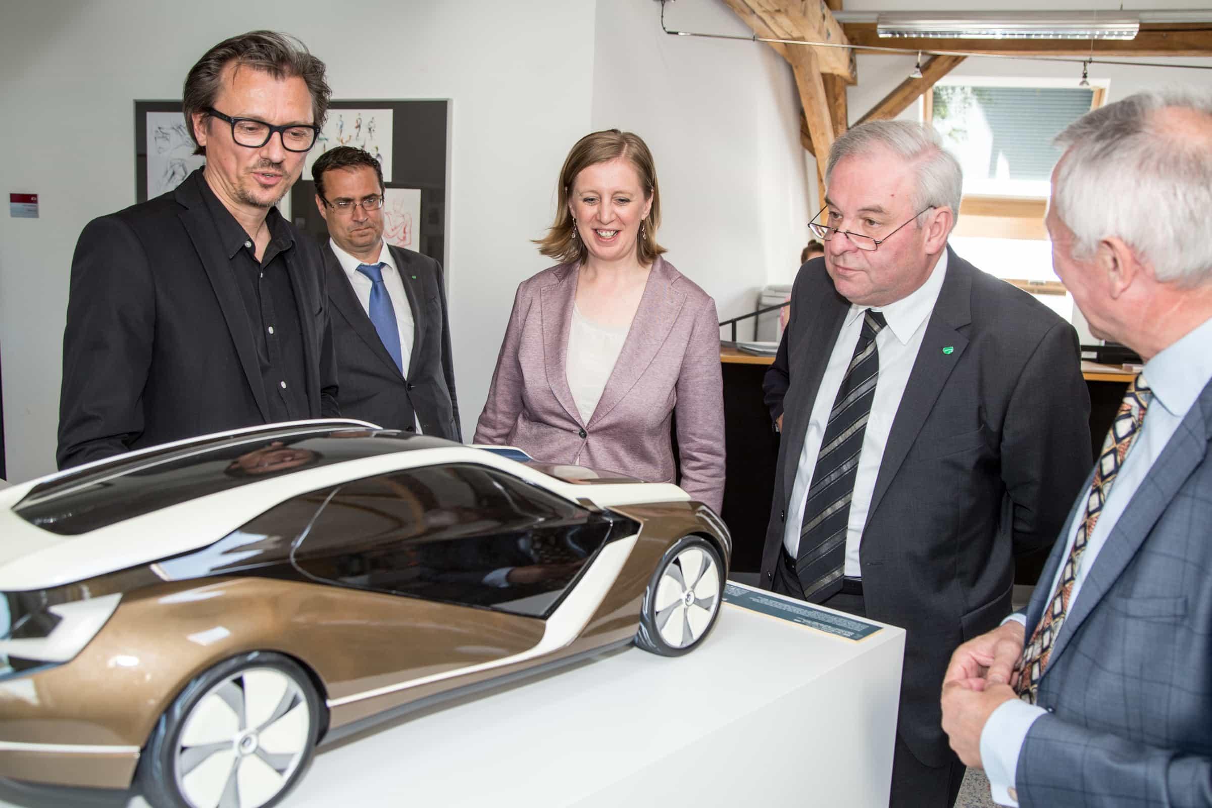 """Die Landesrätin vor einem Modellauto des Studiengangs """"Industrial Design"""""""