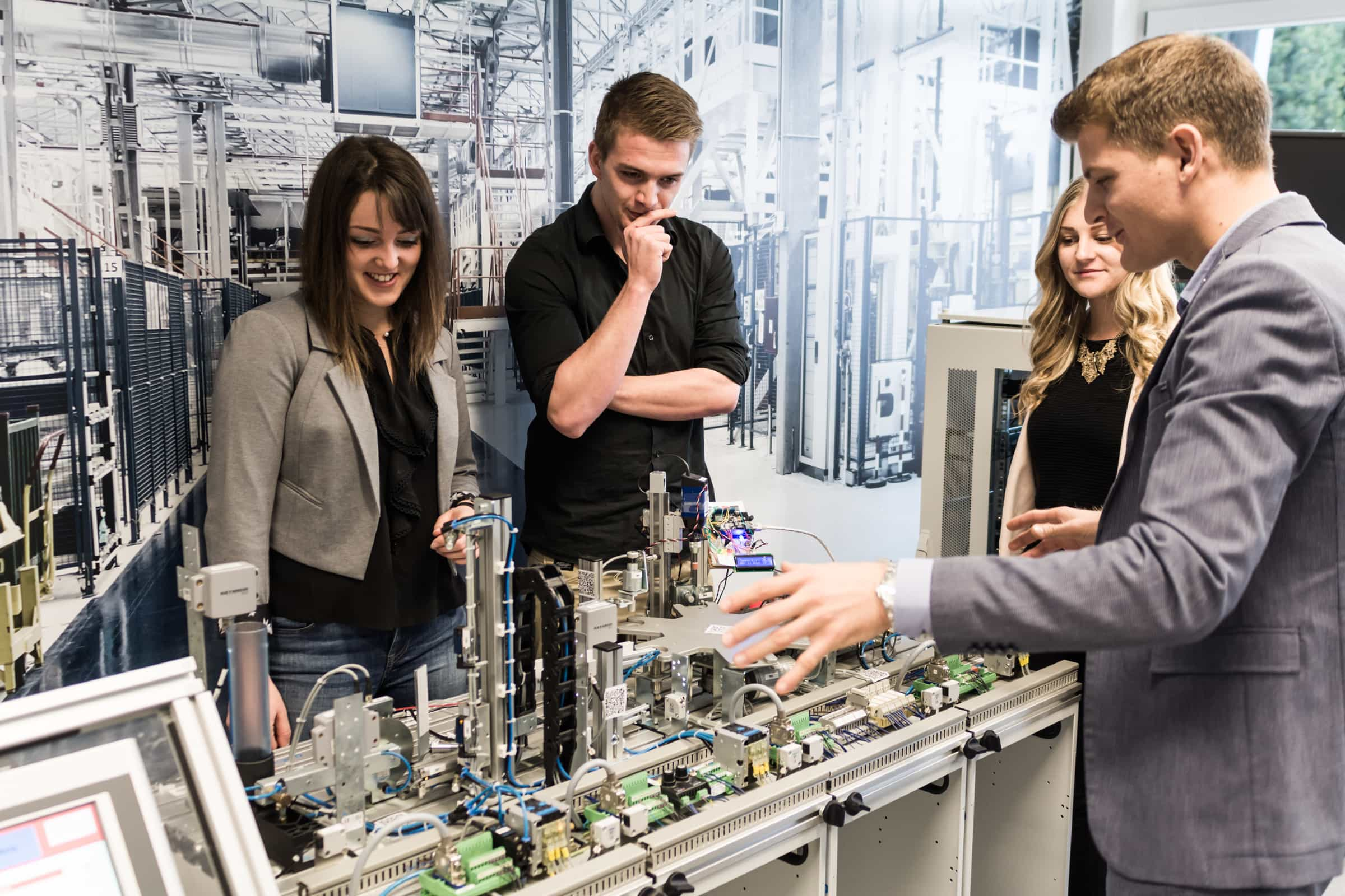 Vier Personen in einem technischen Labor sprechen über die Infrastruktur.