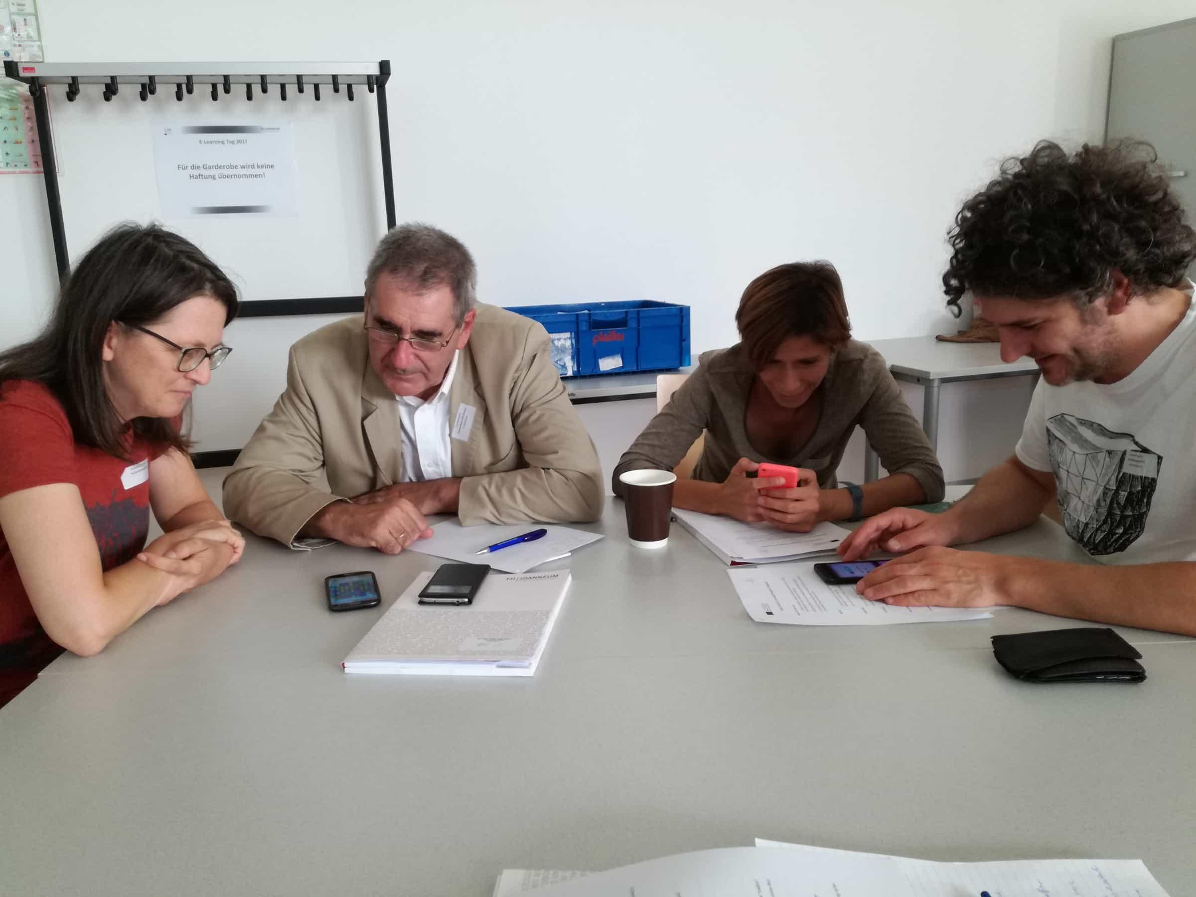 Teilnehmerinnen und Teilnehmer beim Spielen mit ihren Smartphones.