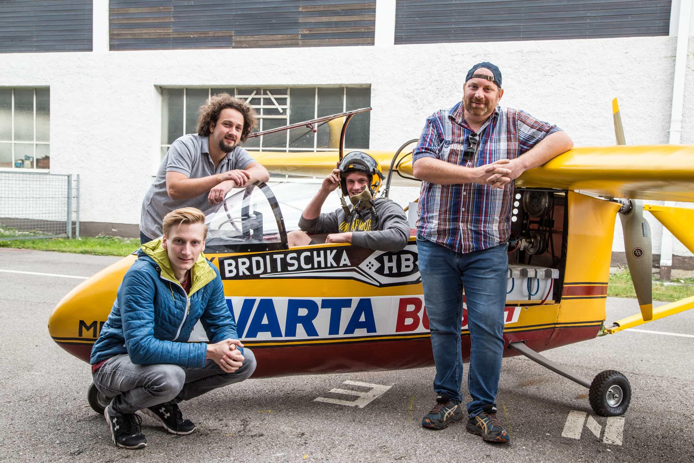 Vier Studierende posieren neben einem restaurierten E-Flieger.
