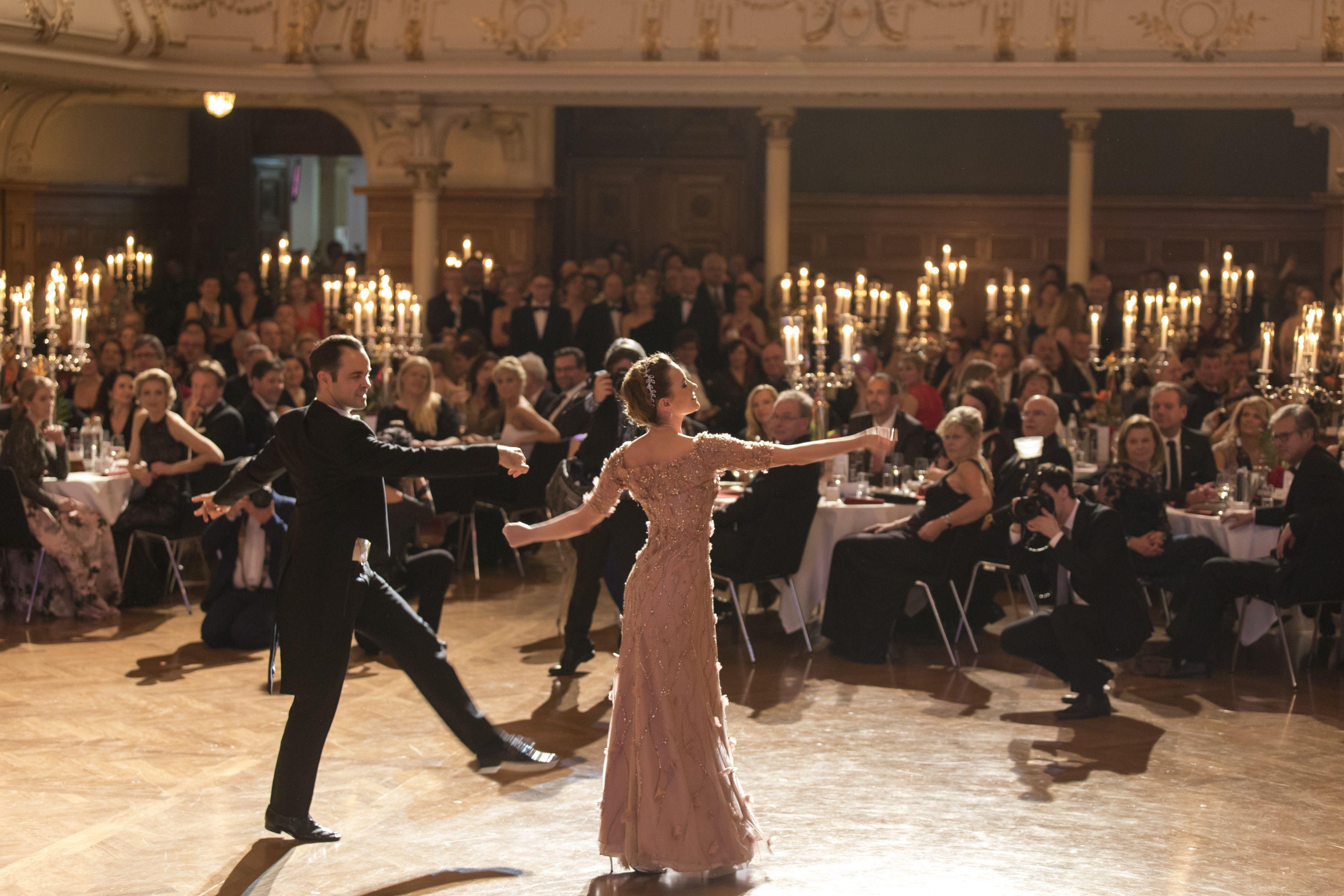 Tanzendes Pärchen mit Personen im Hintergrund im Stefaniensaal.