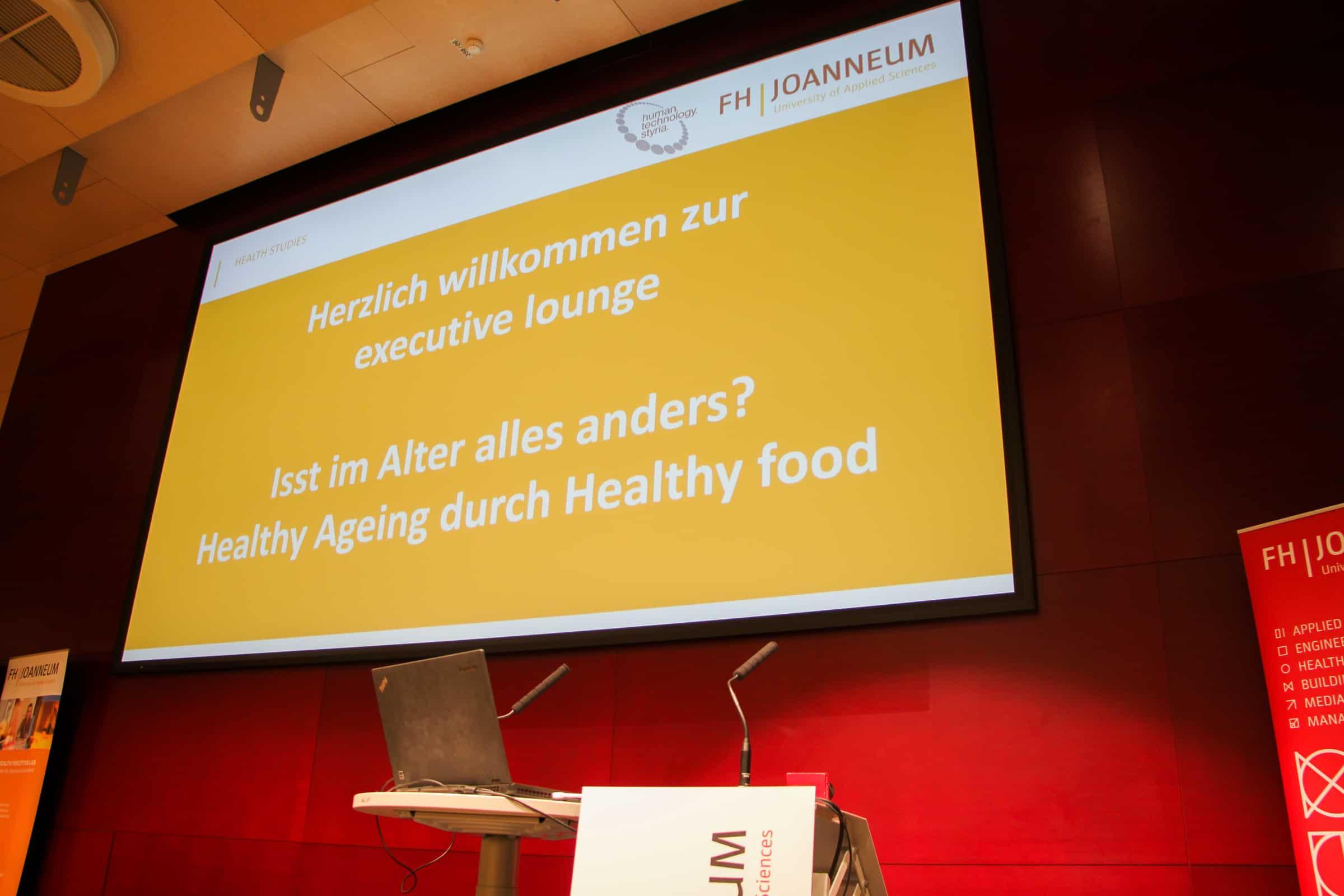 Powerpoint-Präsentation mit Titel der Veranstaltung an der Leinwand des Audimax der FH JOANNEUM.