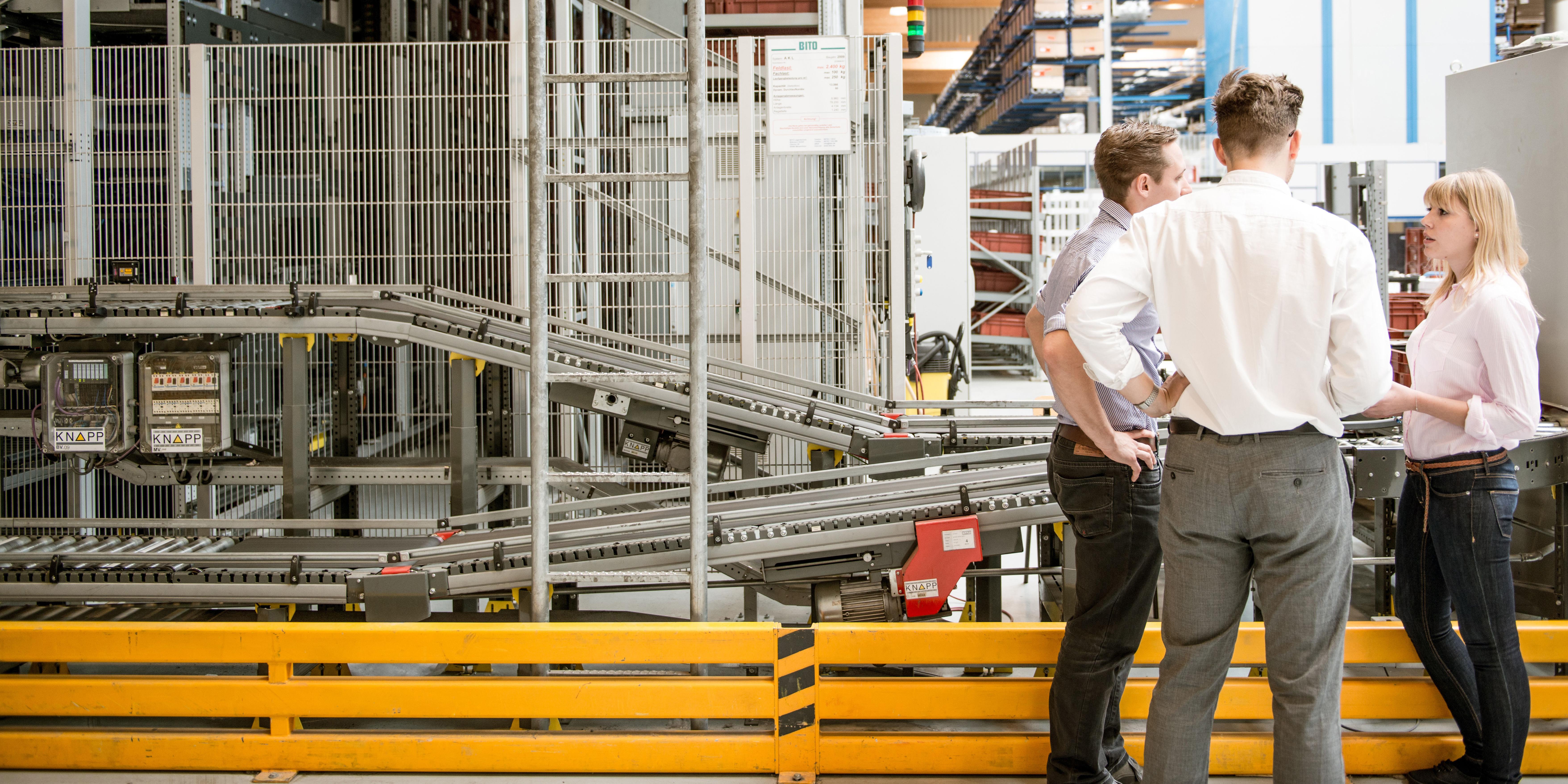Drei junge Menschen unterhalten sich in einer Fabrikshalle.