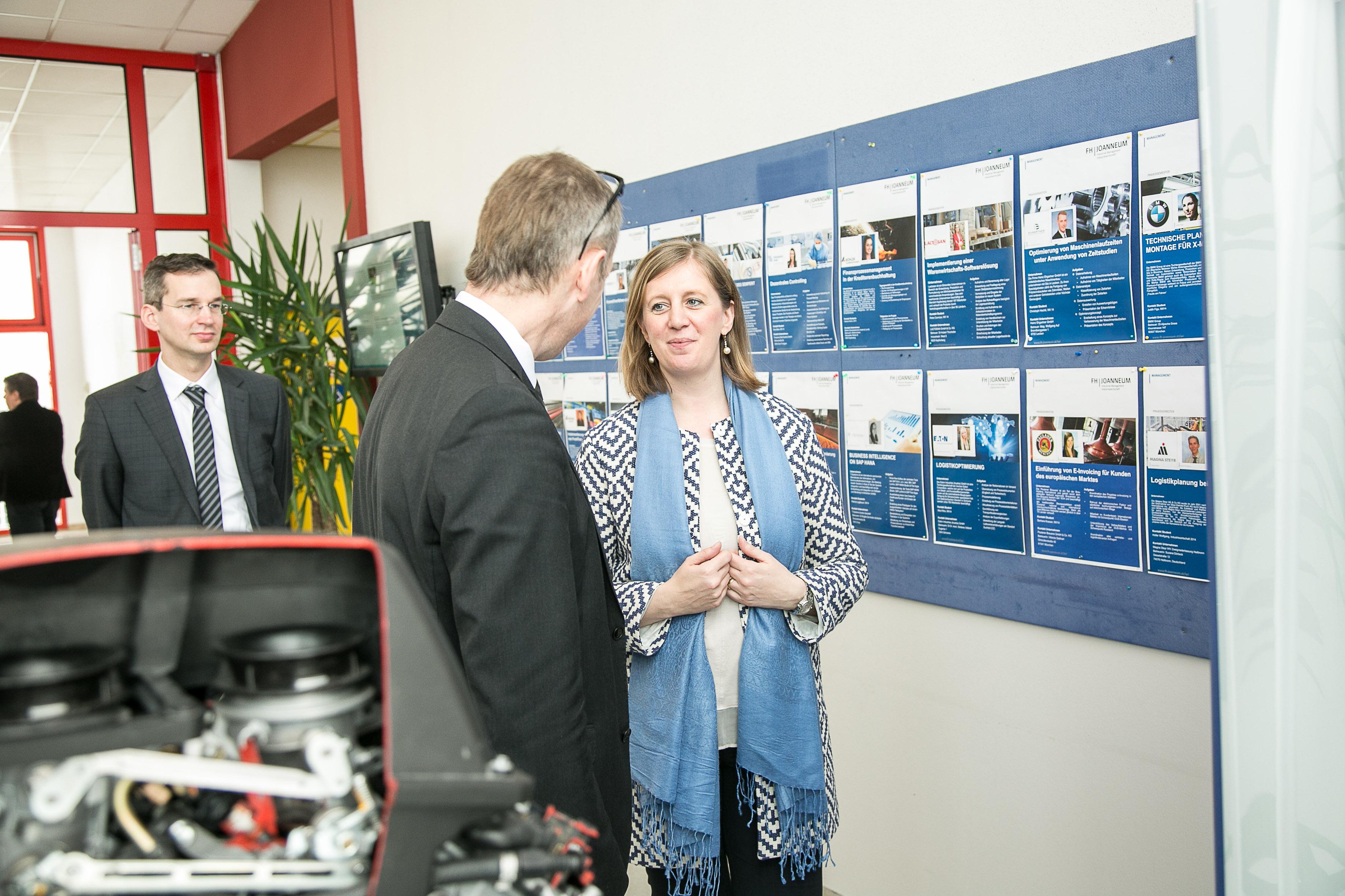 Zwei Personen im Gespräch vor einer Wand mit Projektbeschreibungen.