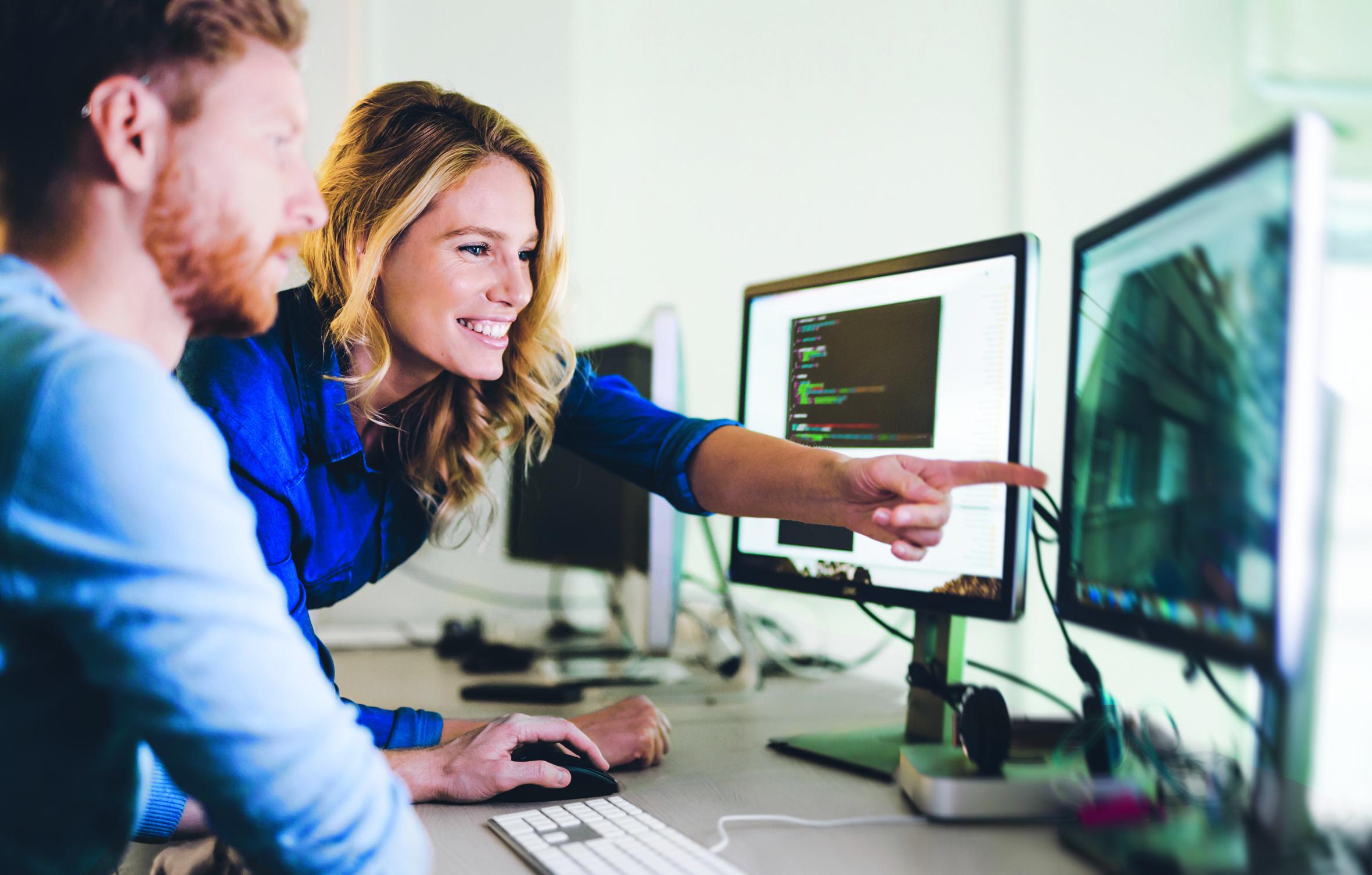 Zwei Studierende vor einem Computer arbeitend.