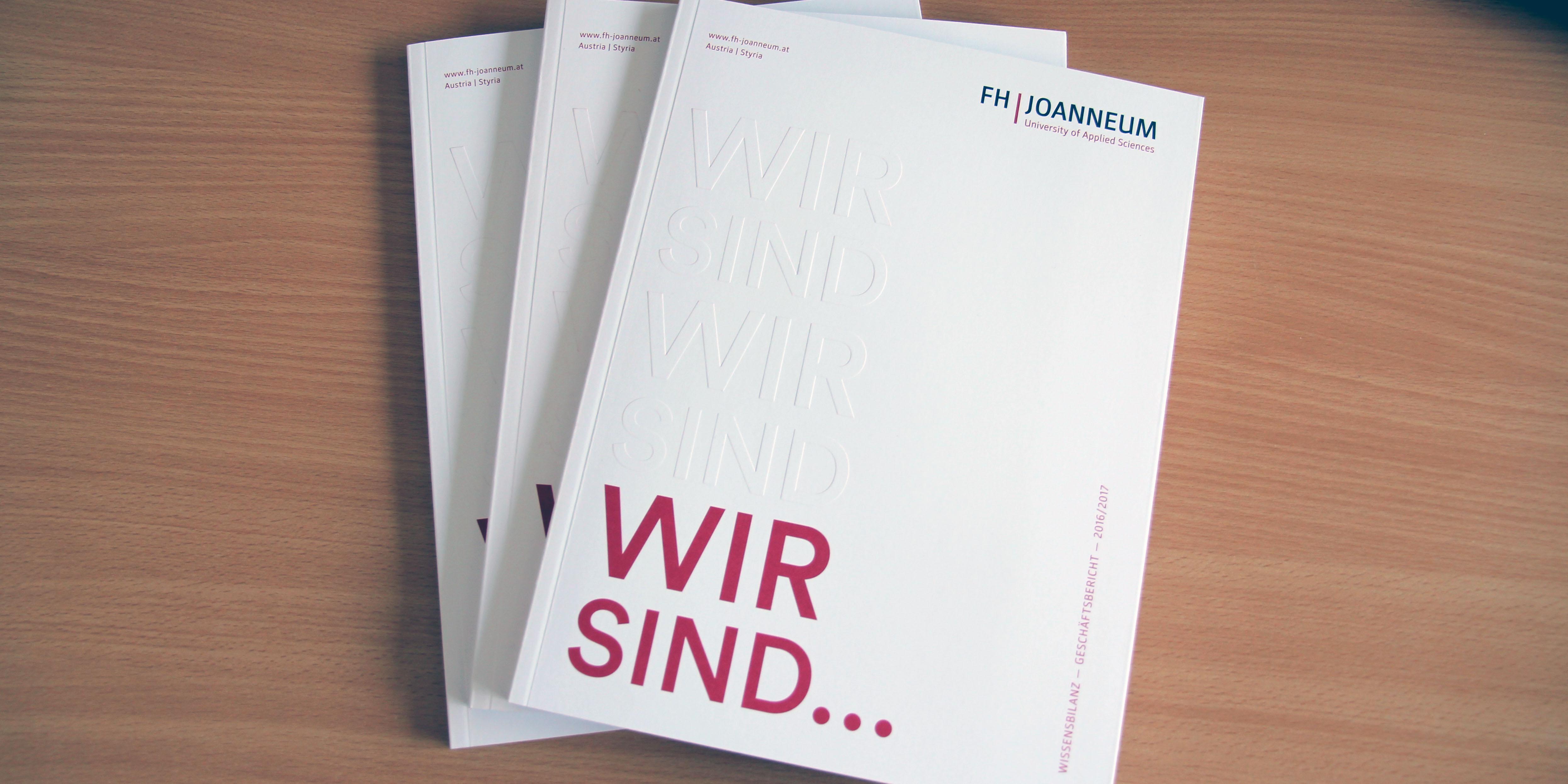 Drei Exemplare des Annual Reports auf einem Tisch.