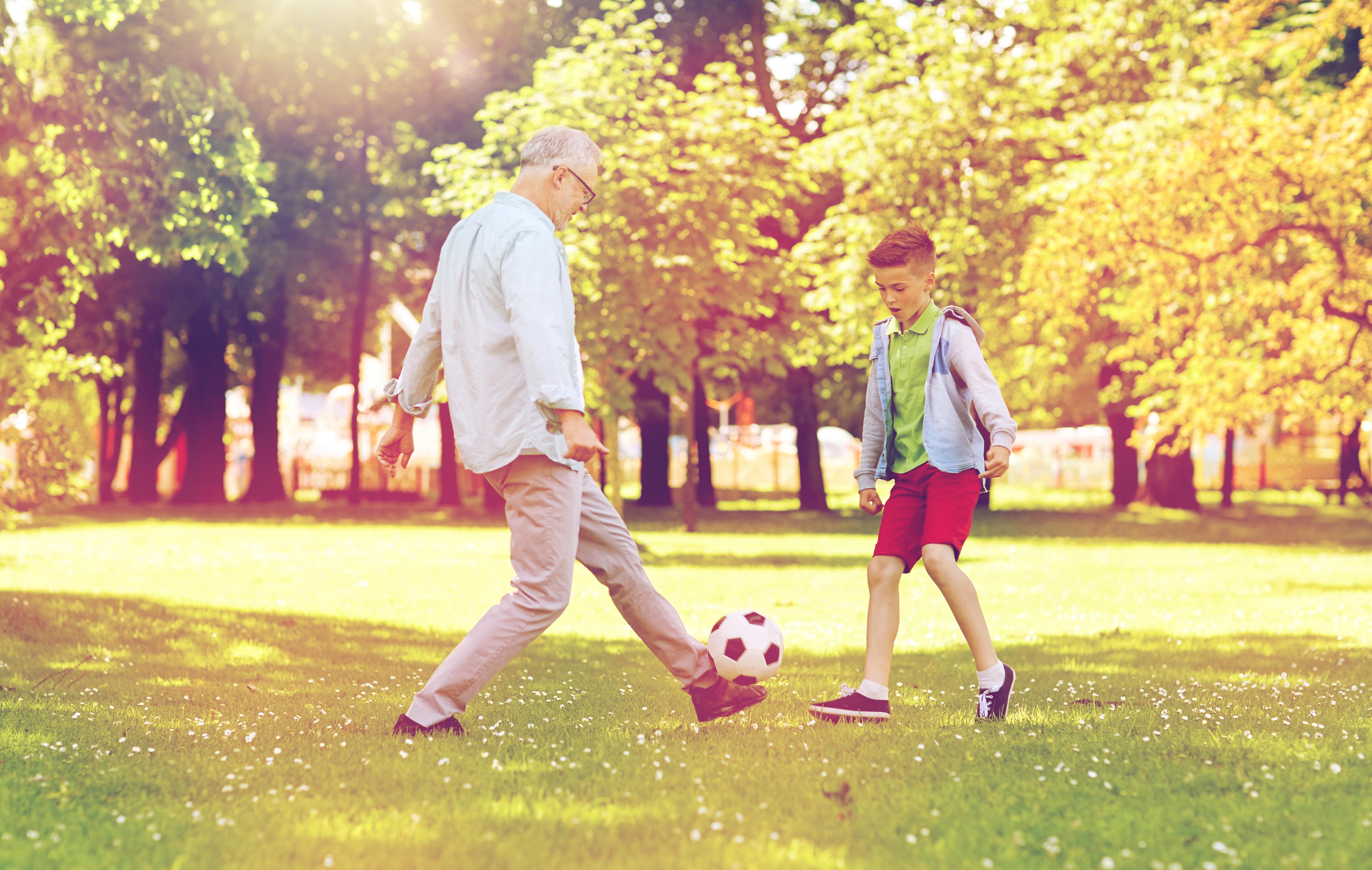 Ein älterer Mann spielt mit einem Jungen Fußball