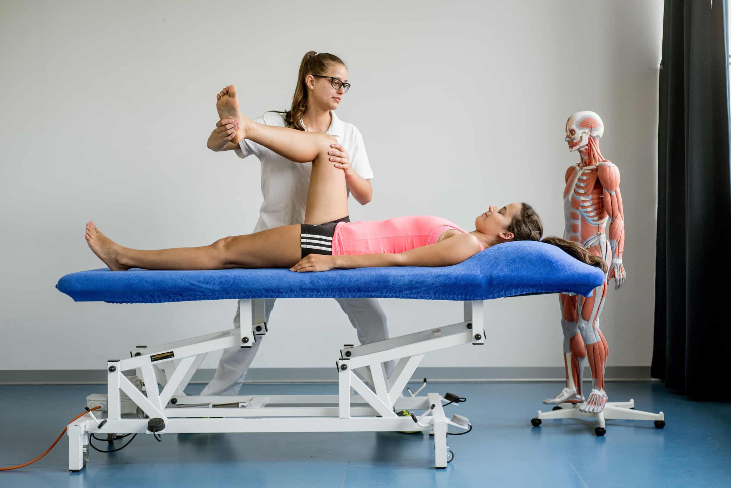 Dame auf einer Liege in physiotherapeutischer Behandlung einer anderen Frau