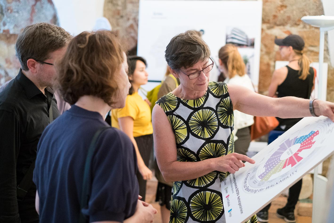 Alexandra Würz-Stalder mit anderen Besucherinnen und Besuchern in der Ausstellung mit einer Tafel in der Hand.