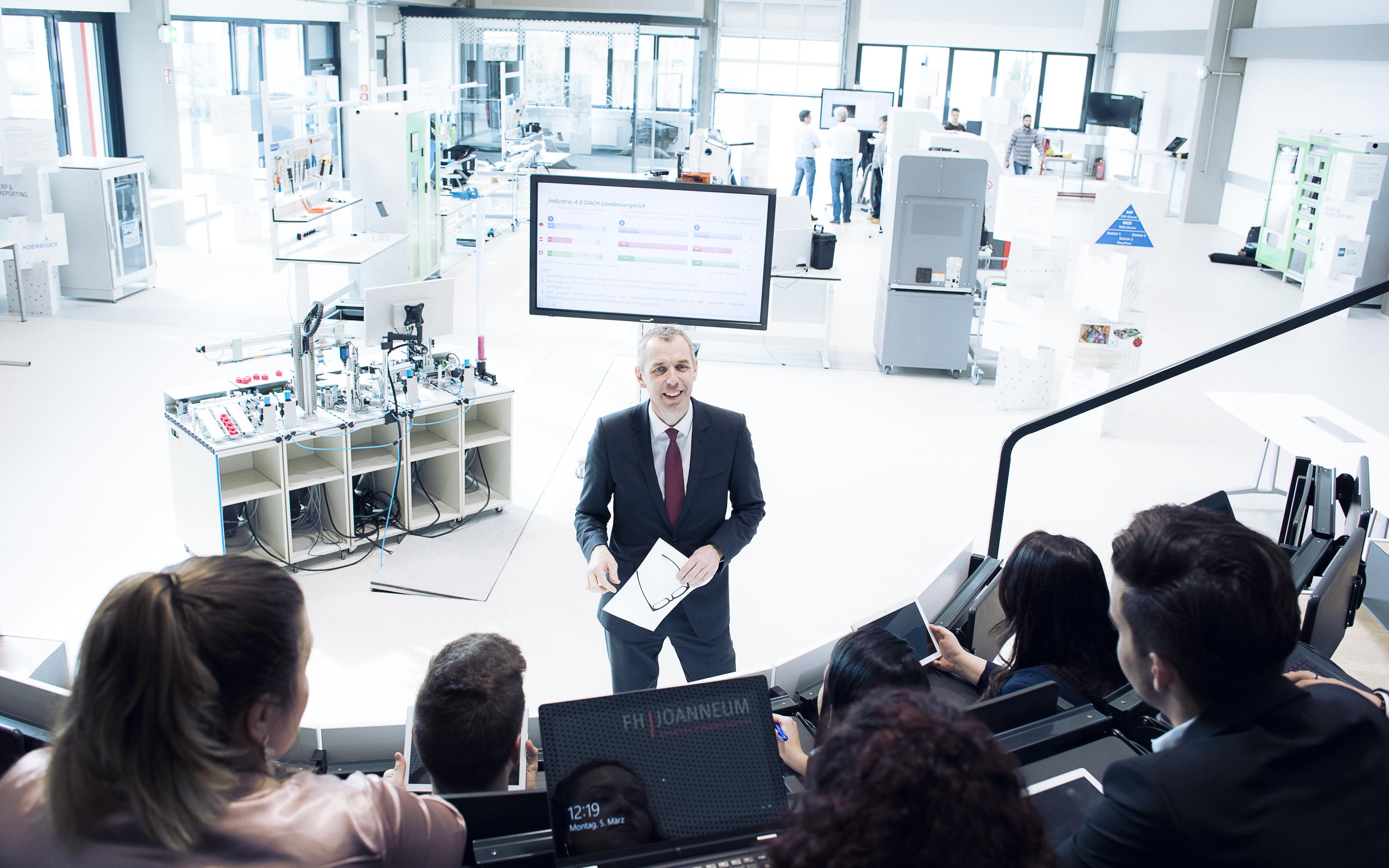 Lehrender mit Smart Production Lab im Hintergrund.