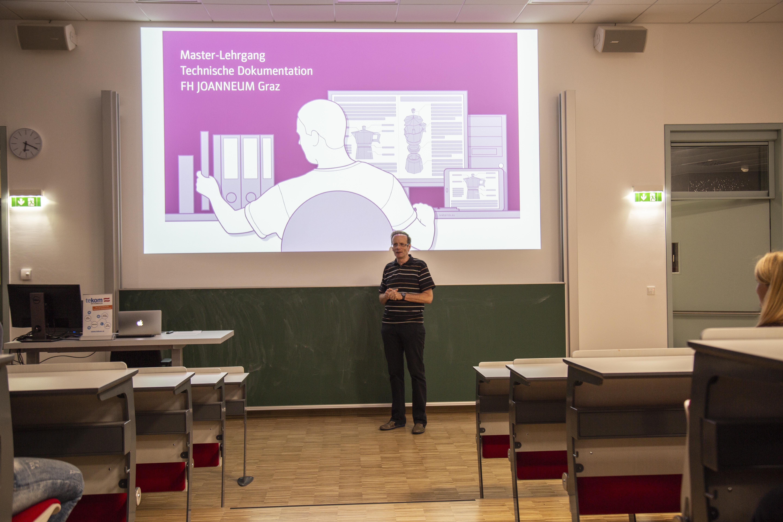 Person bei Vortrag mit Präsentation im Hintergrund.