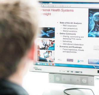 Mann sieht auf eingeschalteten Computerbildschirm.