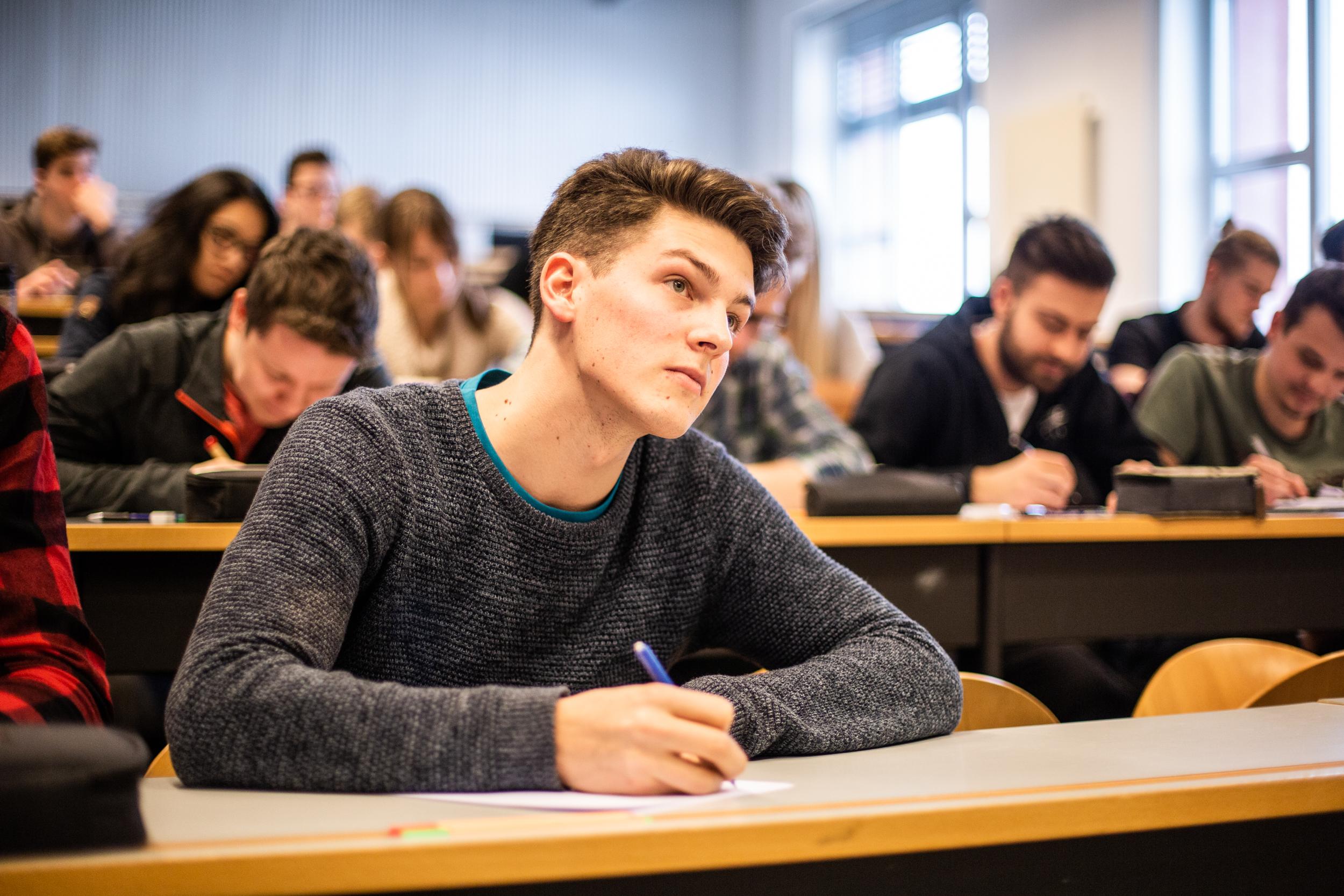 Matthias Grüner sitzt in der Vorlesung, schreibt mit und hört aufmerksam zu.