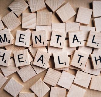 Das Wort Mental Health, aus quadratischen Holzstücken mit Buchstaben darauf gebildet.