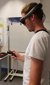 Mann trägt eine Augmented-Reality-Brille und hält einen Controller in der Hand.