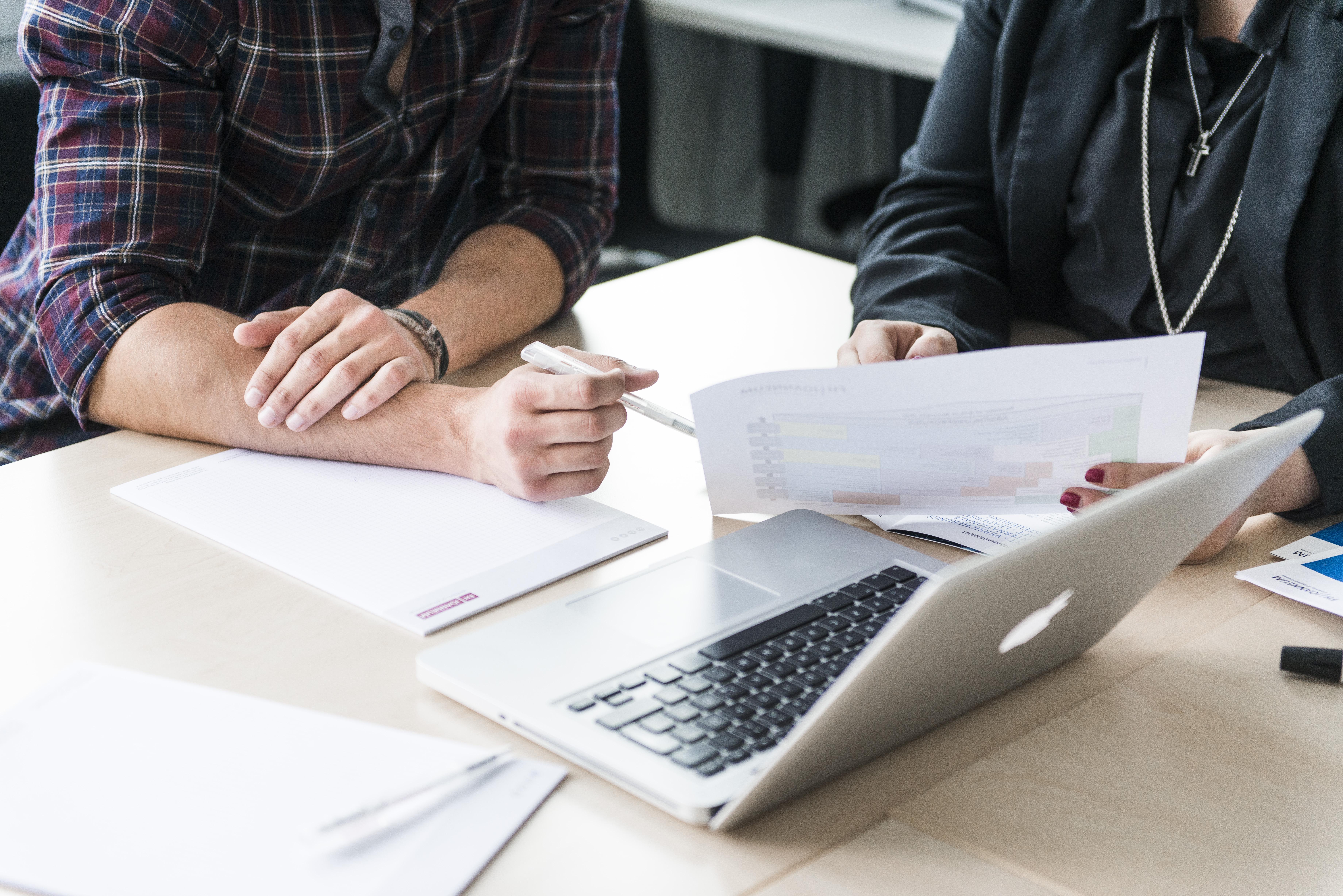 Zwei Studierende sitzen vor einem Laptop.