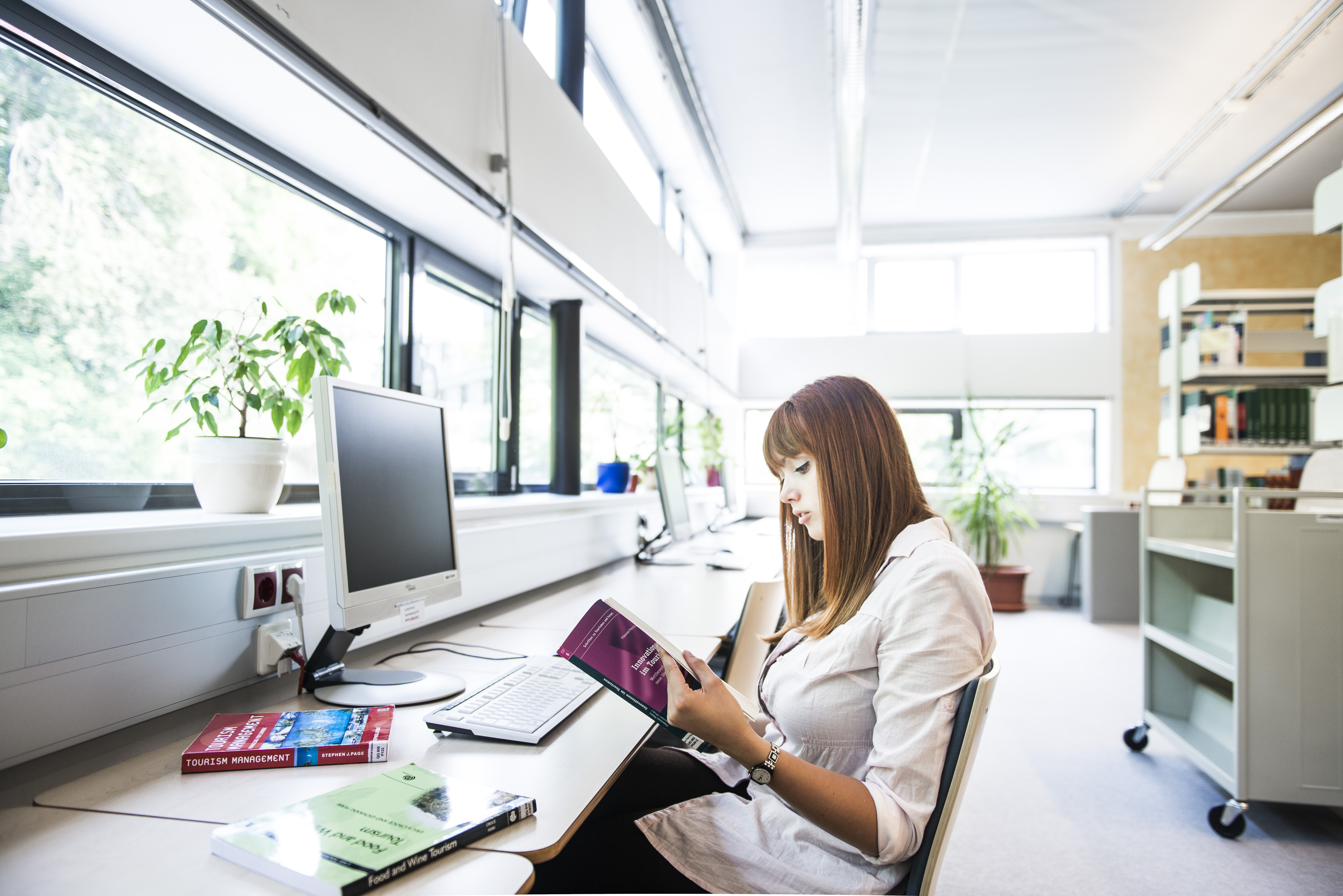 Studentin sitzt in der Bibliothek der FH JOANNEUM Bad Gleichenberg und blättert in einem Buch.