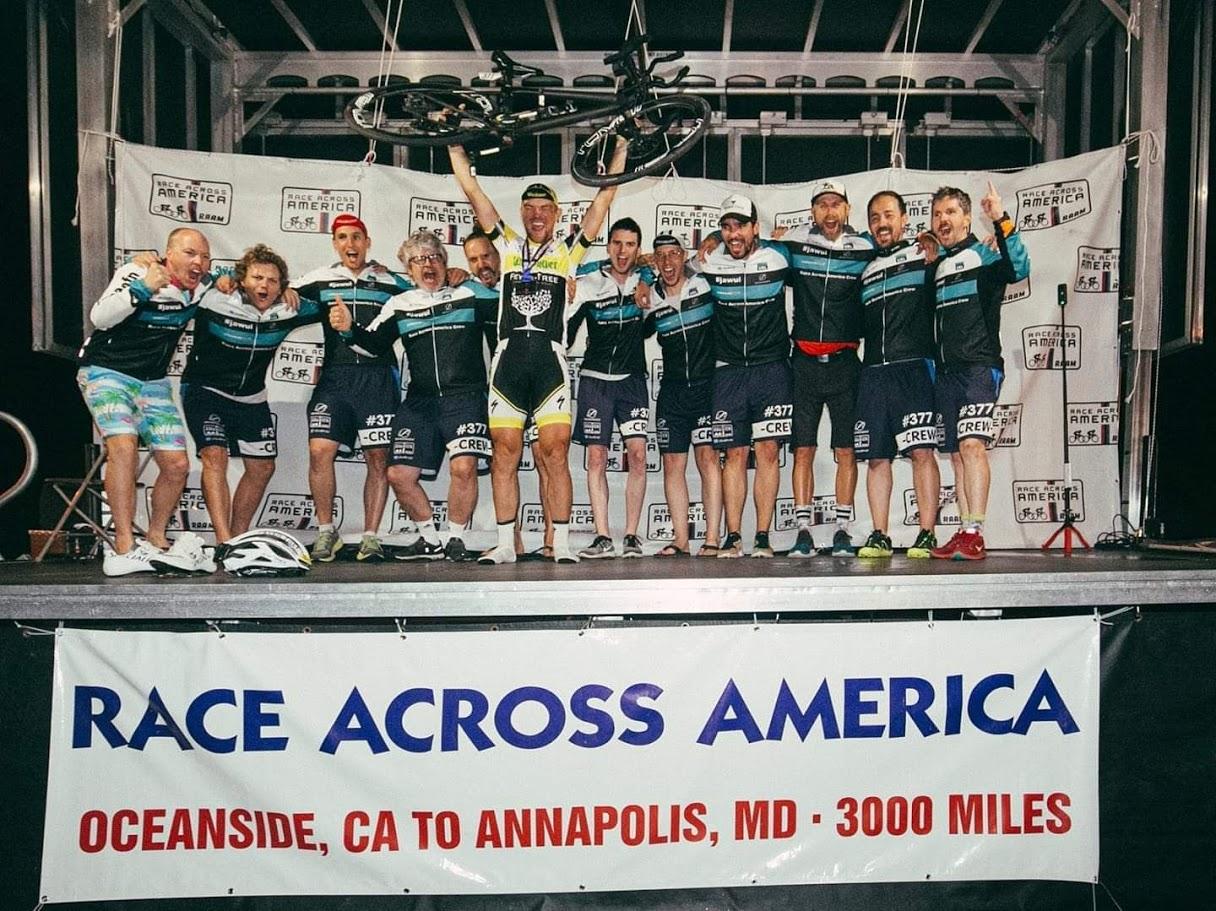 Bild von der Siegerehrung beim Race Across America 2019. Christoph Strasser stemmt sein Fahrrad in die Höhe. Sein Team rund um ihn jubelt mit.