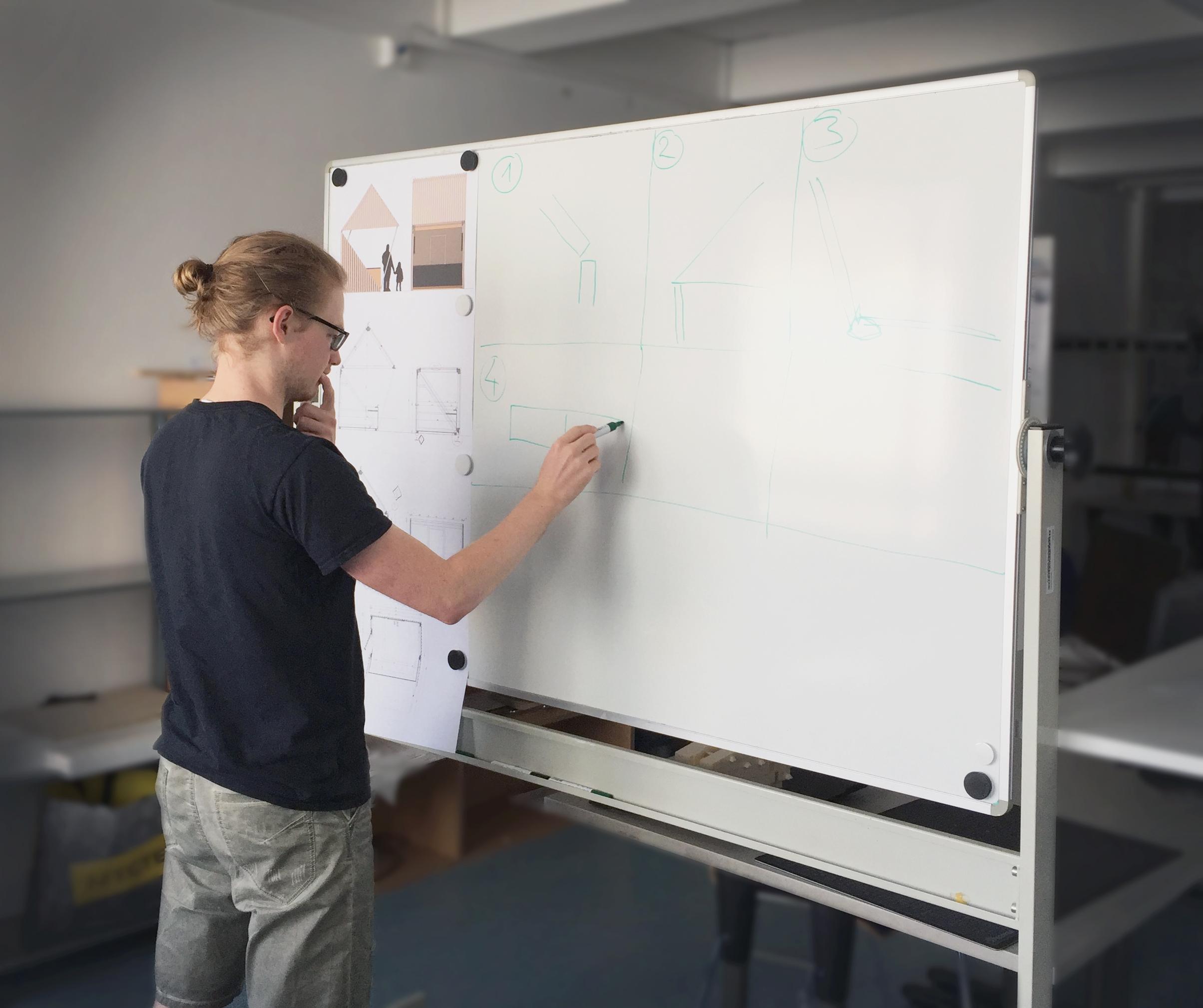 Peter Hintermayer steht vor einer weißen Tafel und hält einen Stift in der Hand, mit dem er etwas auf die Tafel zeichnet.
